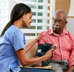 caregiver checking patient's blood pressure